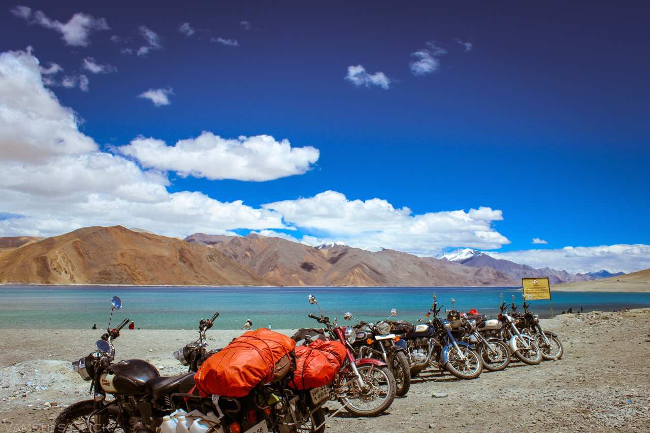 Many bikes parked at the banks of a lake