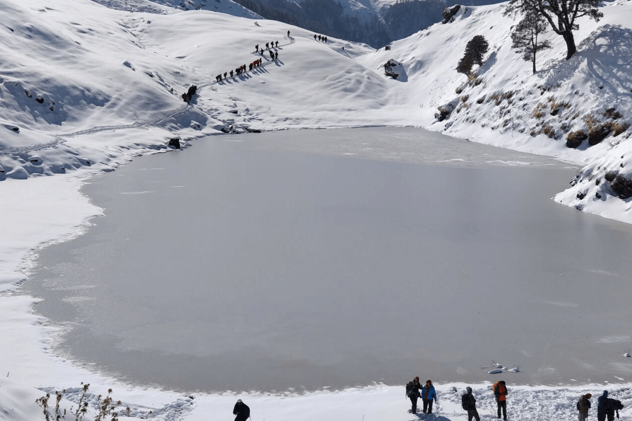 Groups of trekkers converge at the frozen Brahmatal on a winter trek