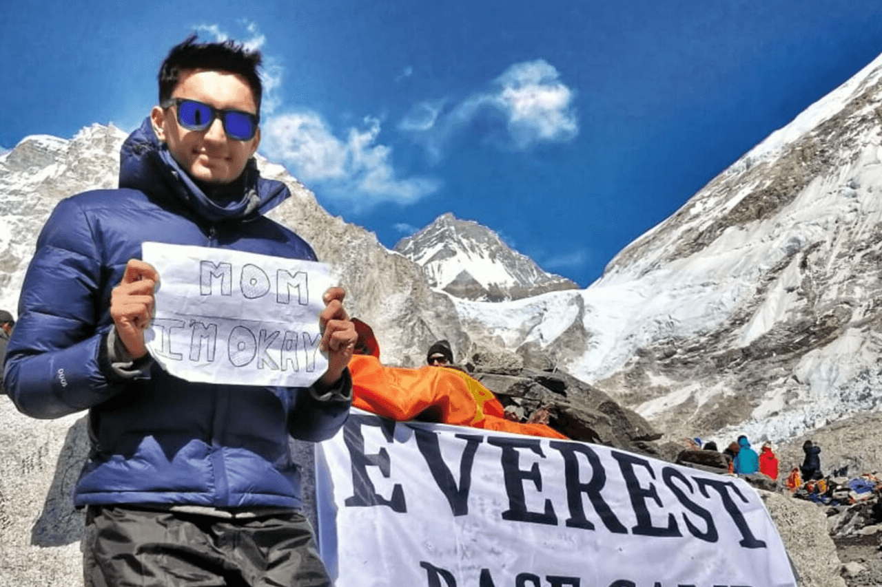 Trekker standing at Everest Base Camp sign with note in hands.