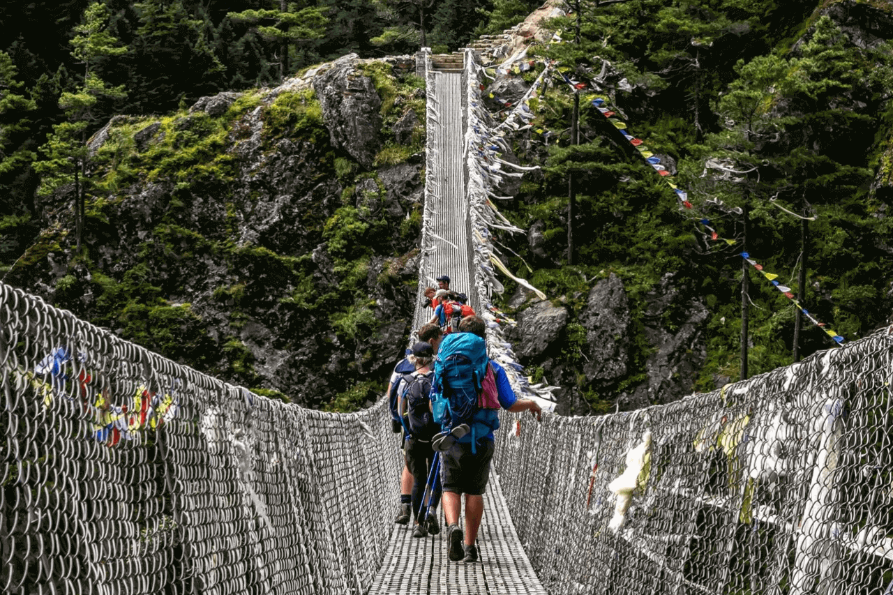 Trekkers walk on suspension bridge in Nepal.