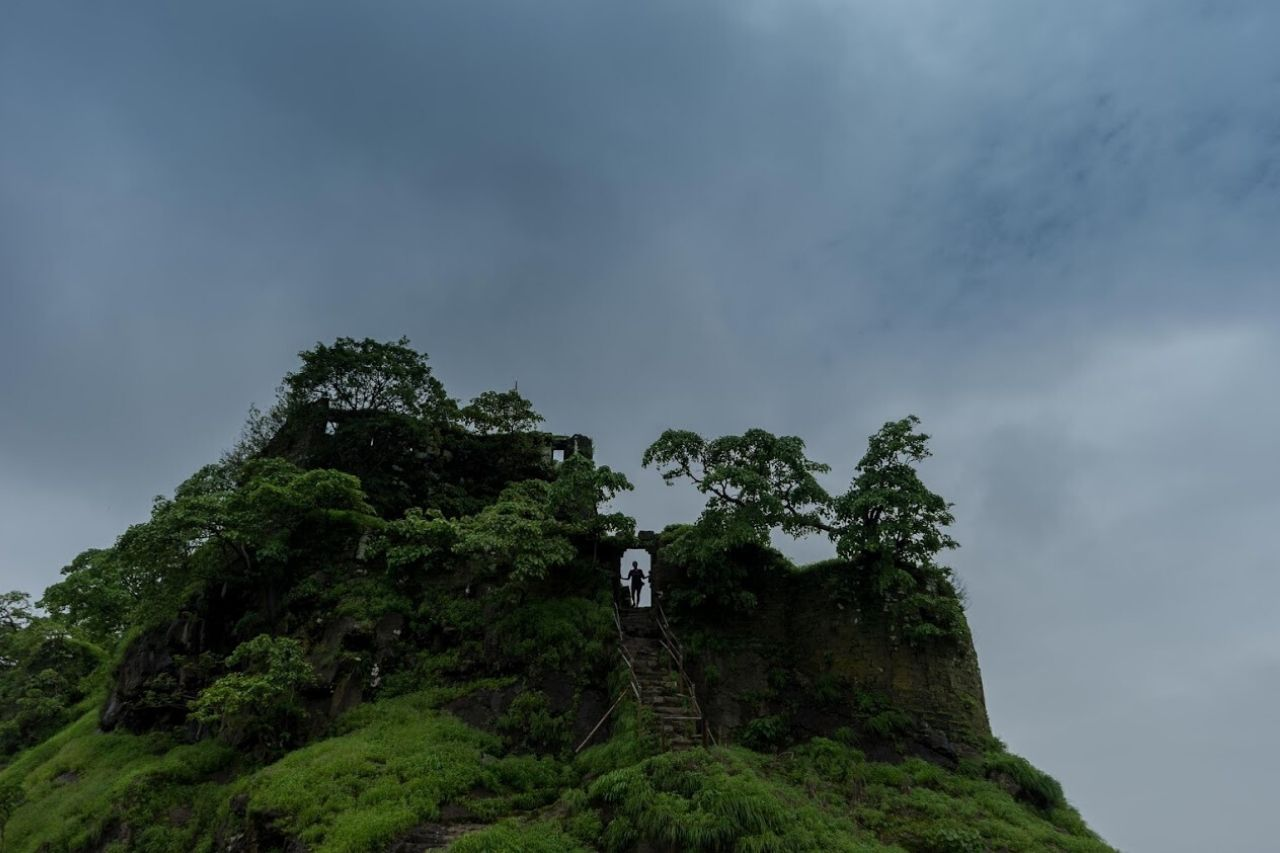 Solo person stands silhouetted atop a hill