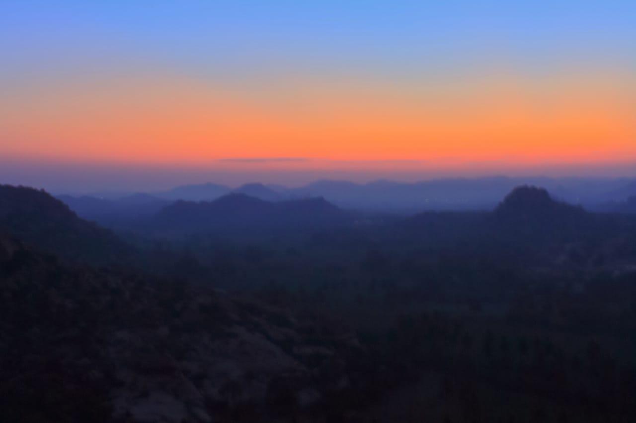 Orange and purple sky lights up a dark horizon