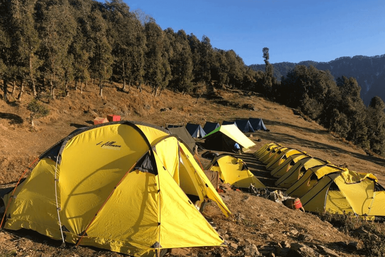 Bright yellow tents stand in a line in the mountains.