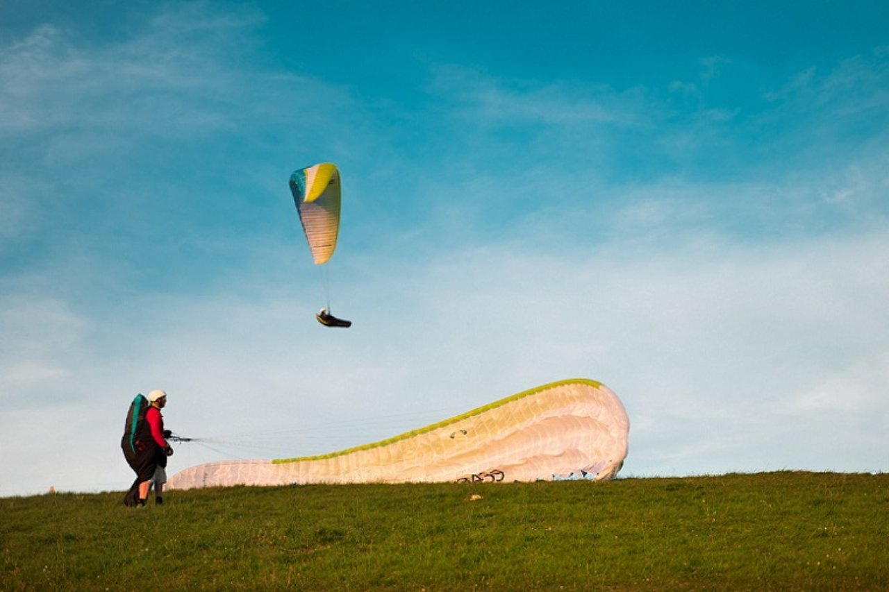A paragliders flies past a snowy mountain slope