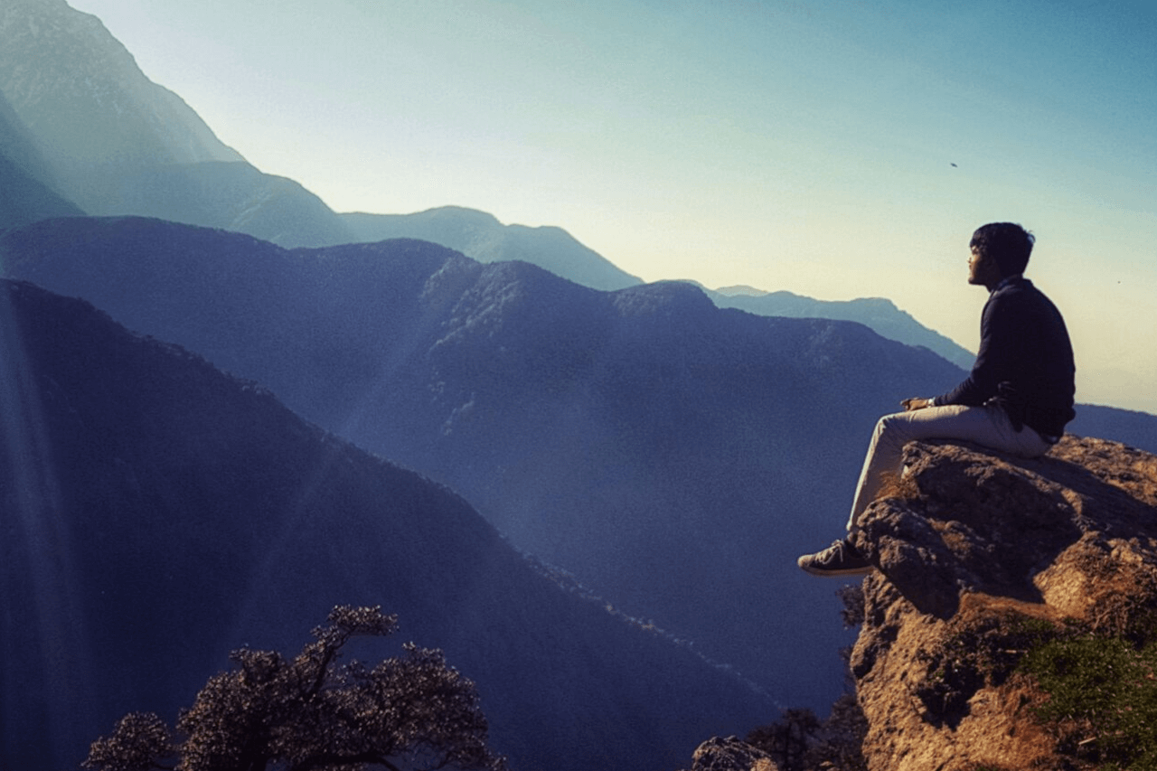 Solo person sits on a rocky ledge looking at mountains.