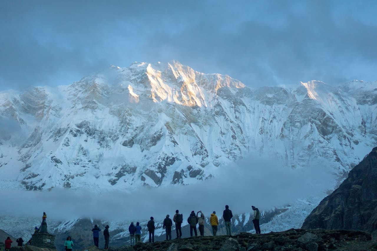 A group of trekkers stand in awe as the sunrays kiss the ginormous mountain peak