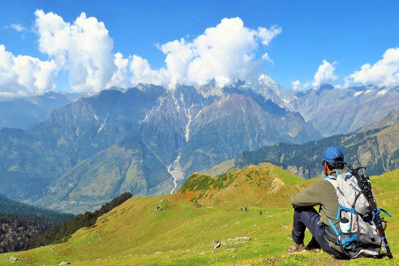 A trekker sits on a meadow enjoying the view of the rolling mountains ahead