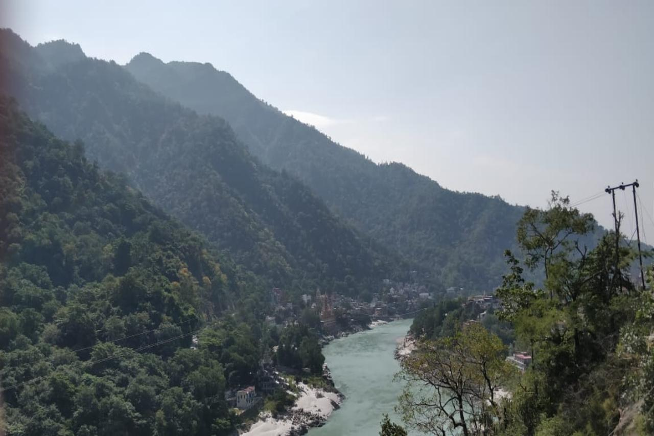 A blue river flowing in front of forested mountains.