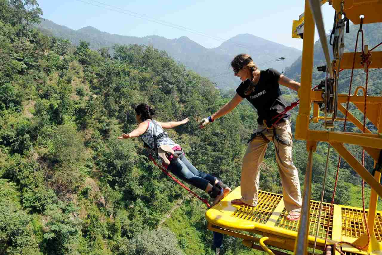 An instructor holding a person on the verge of a platform.