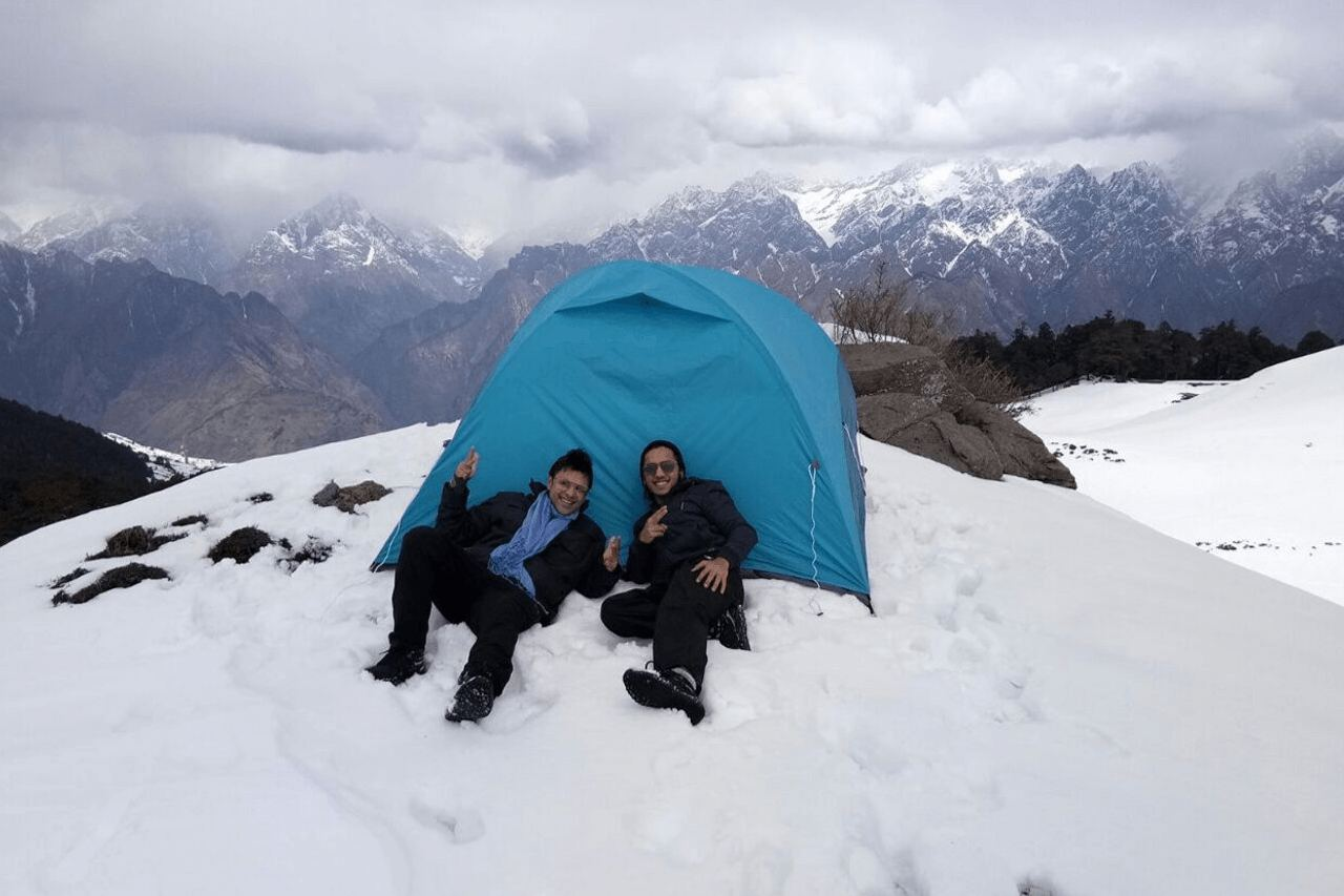 Two trekkers pose outside their alpine tents on a snowy landscape