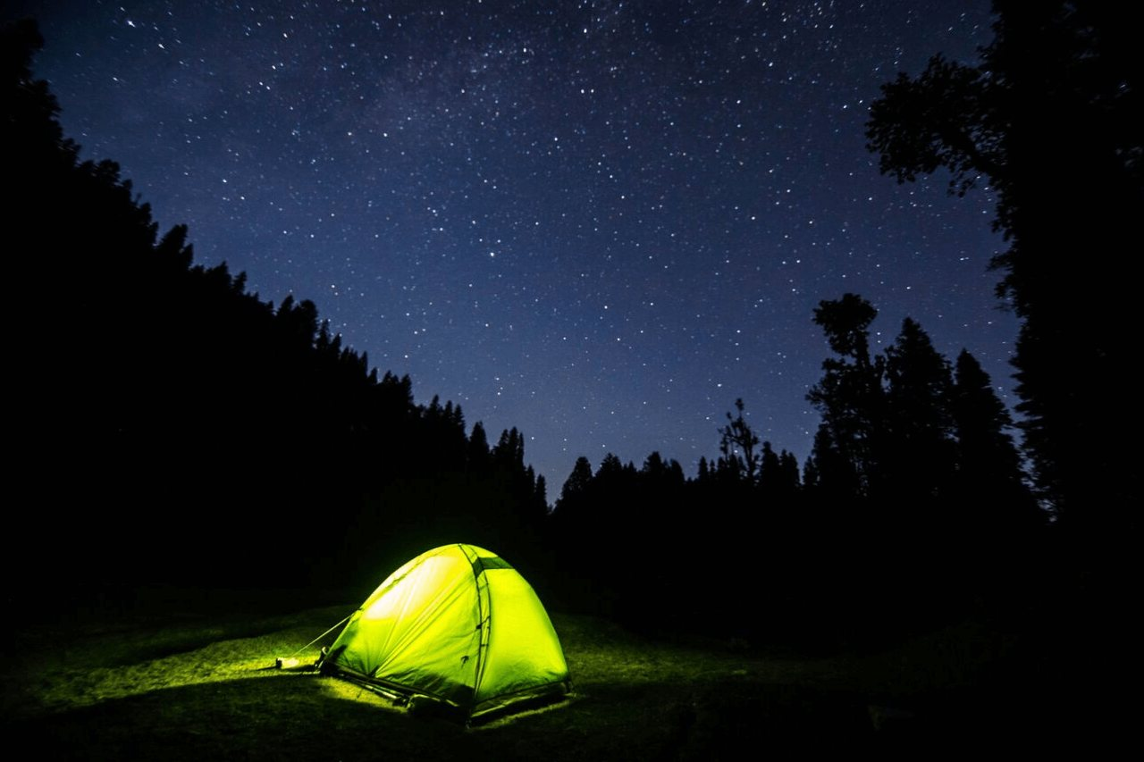 A camping tent in the night under a starry sky