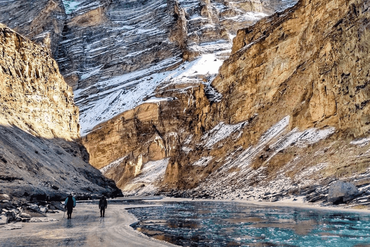 Sun glinting off frozen river while Chadar trekkers walk on the frozen river