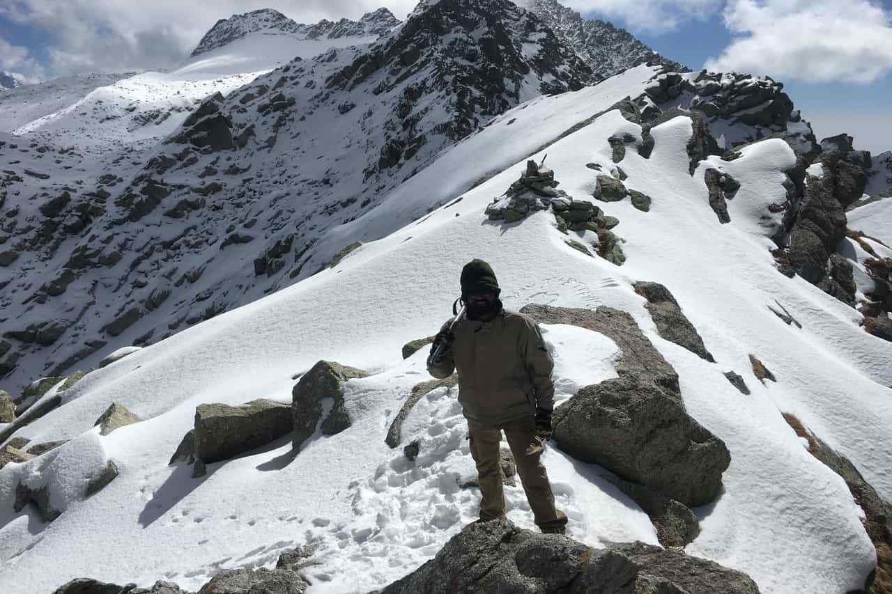 A trekker stands on a mountain ridge covered in snow