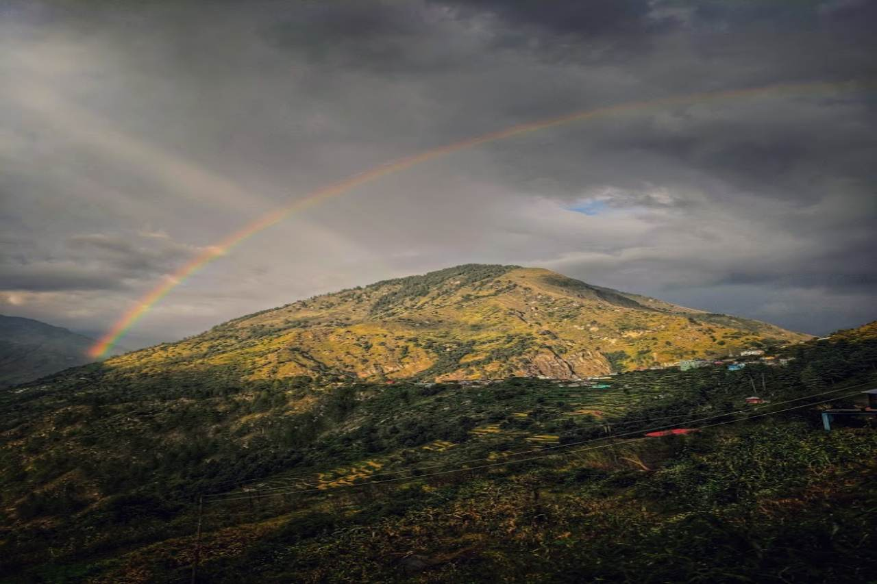 A rainbow breaks out in the grey sky over a mountain peak.