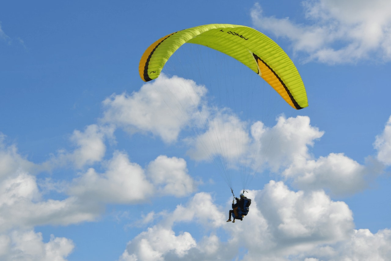 Tandem paragliding flight in a sky with white clouds
