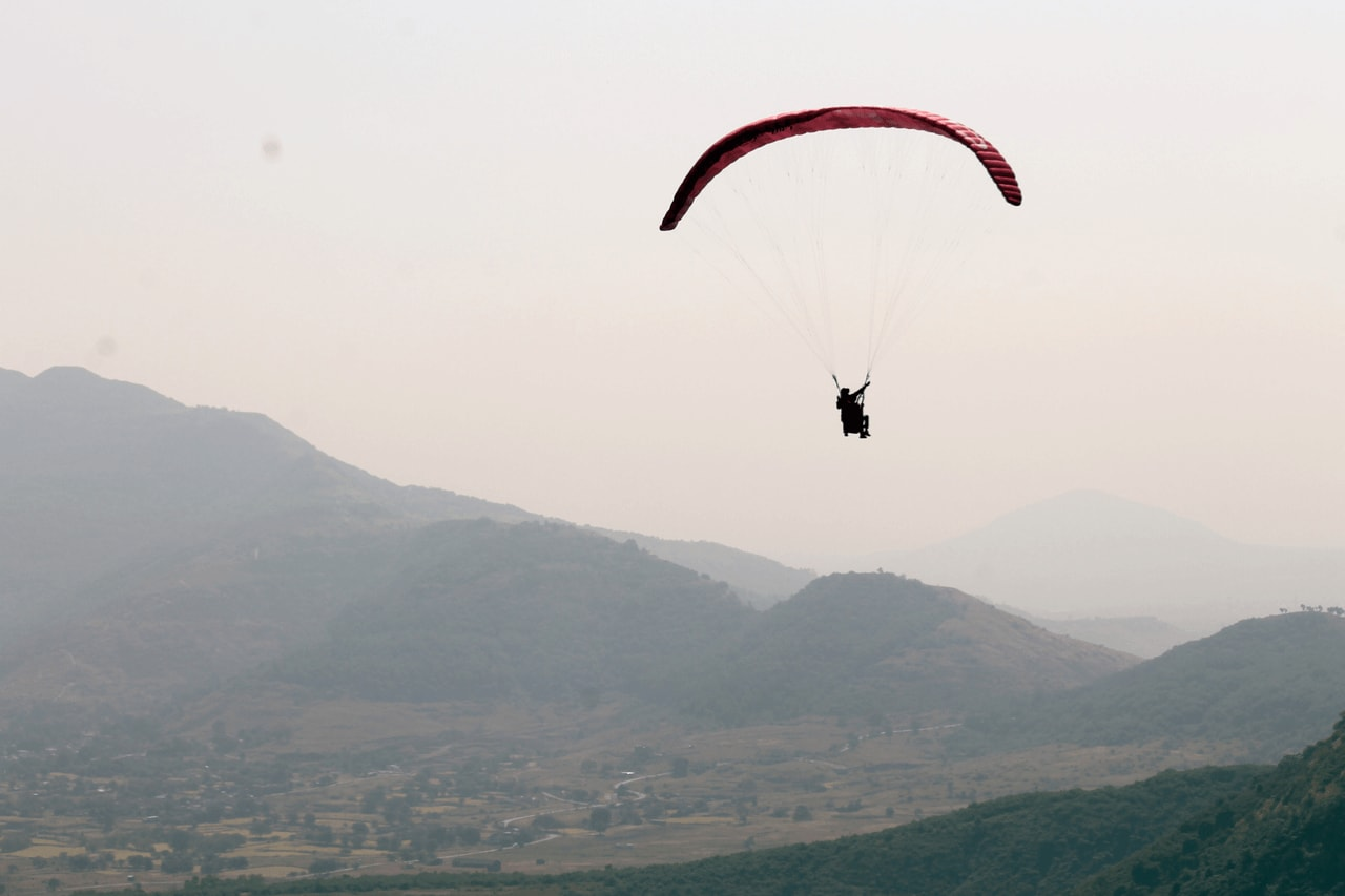 Paraglider with two people soaring into the evening sky