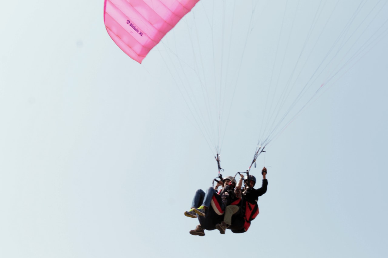 Side angle of tandem paragliding flight with pilot and passeger.