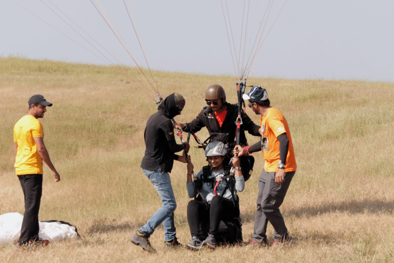 Group of people help tandem paraglider to gear up