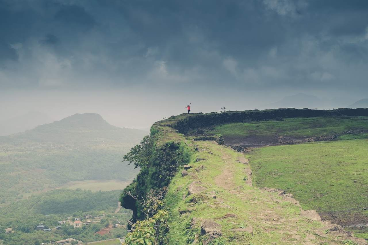 A person poses on the edge of a flat mountain top