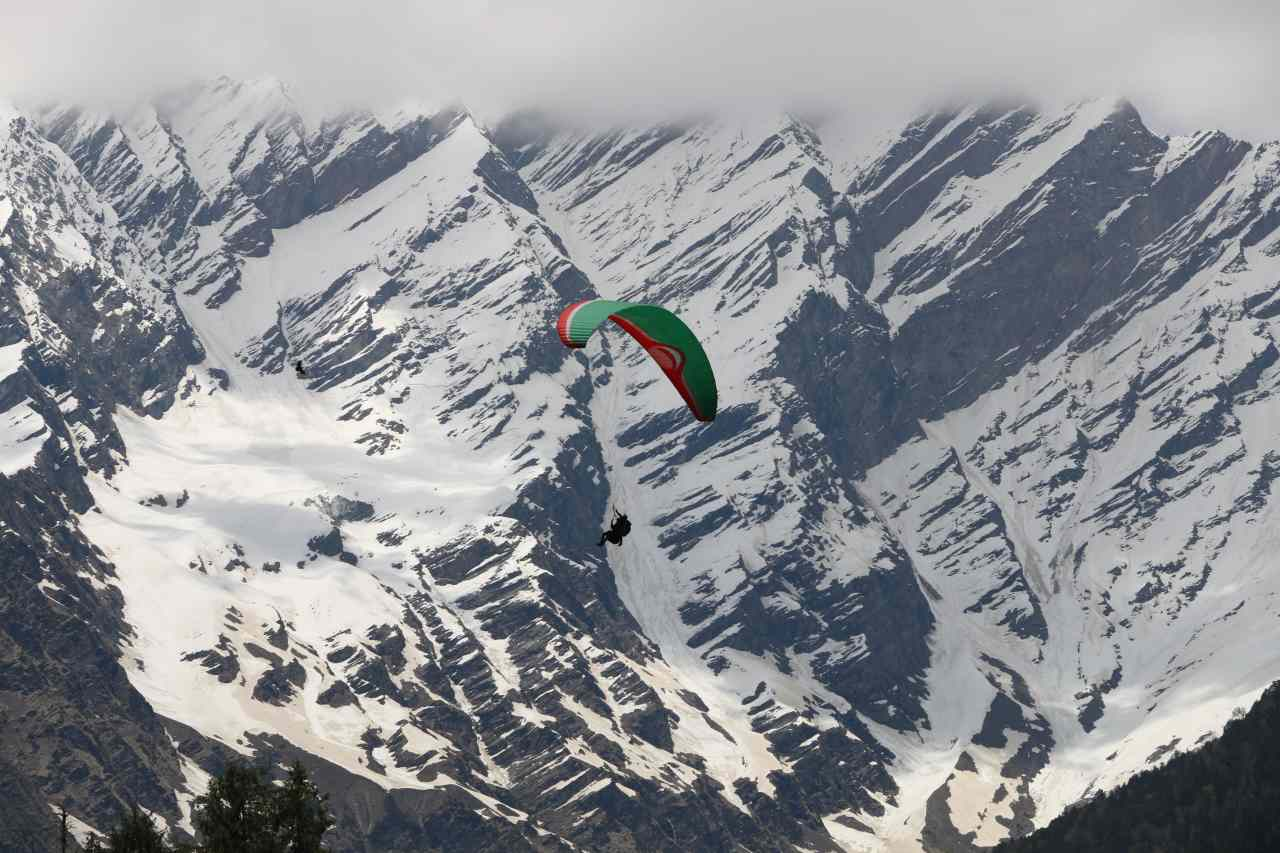 A paraglider flies past a snowy mountain slope.