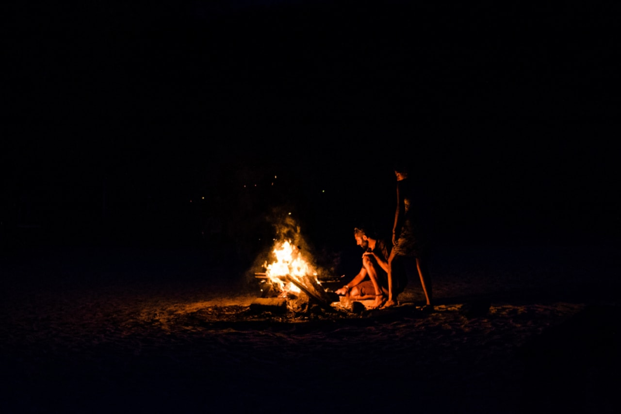 Two people stand near bonfire on a dark night