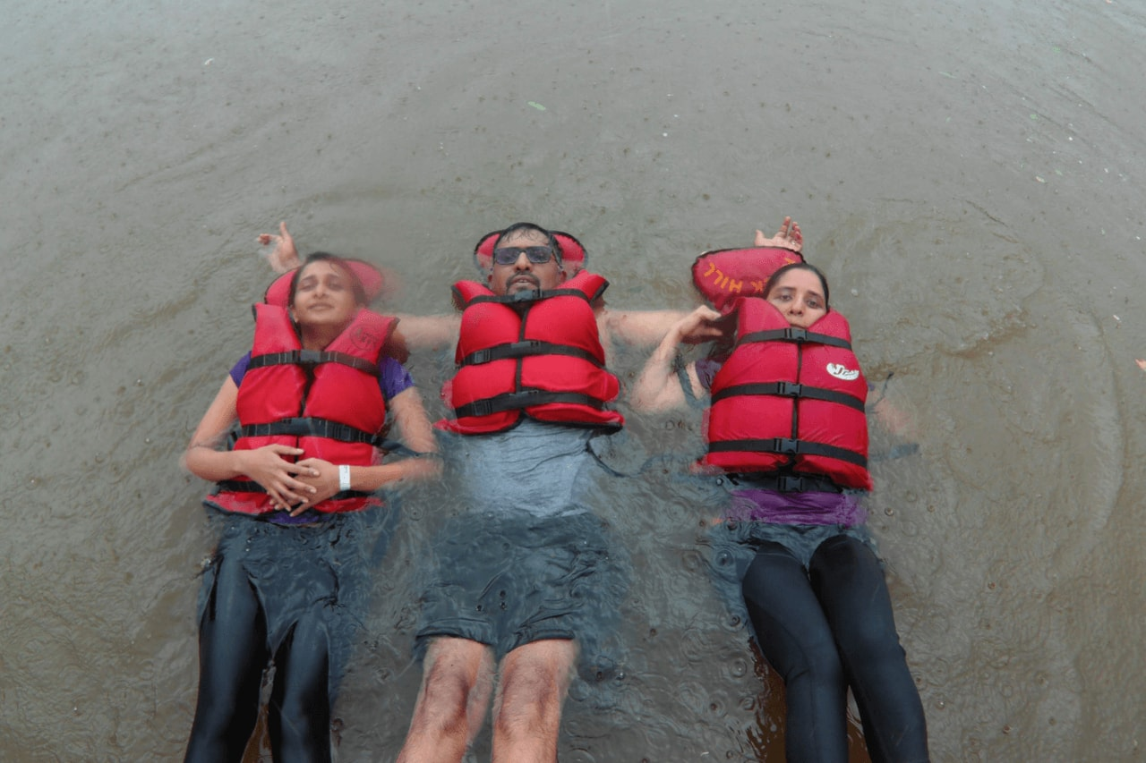 Three people in life jackets floating in river