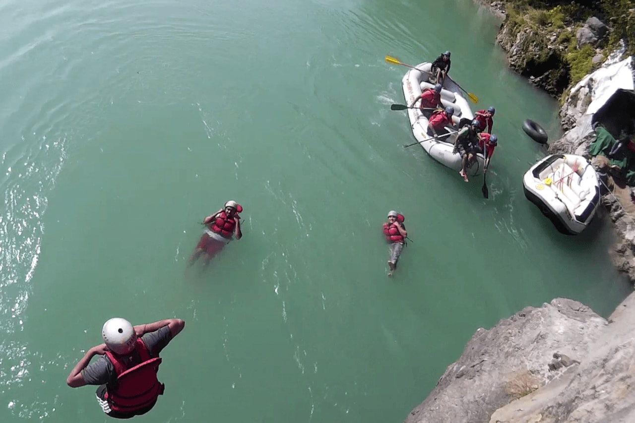 Aerial view of people jumping from cliff into water