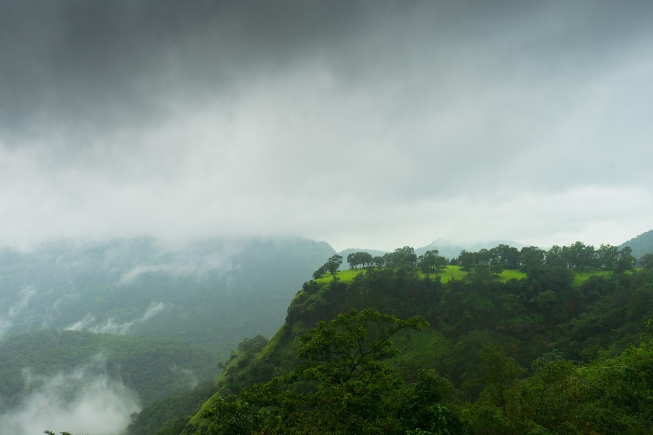An overview of a cliff surrounded by misty mountains.