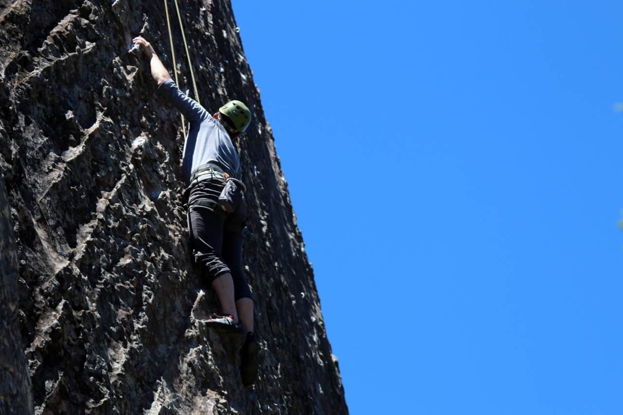 A man rappelling down a rock face.