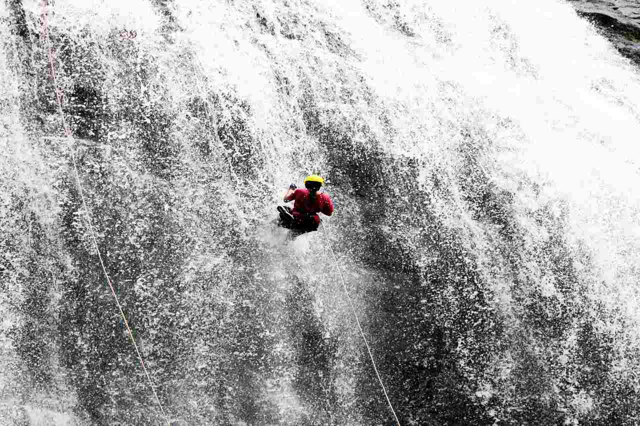 A person rappelling down a rock face with a waterfall flowing in full force.