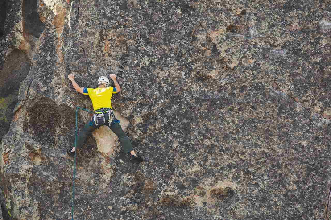 A man in harness holding on to cracks on a rock face