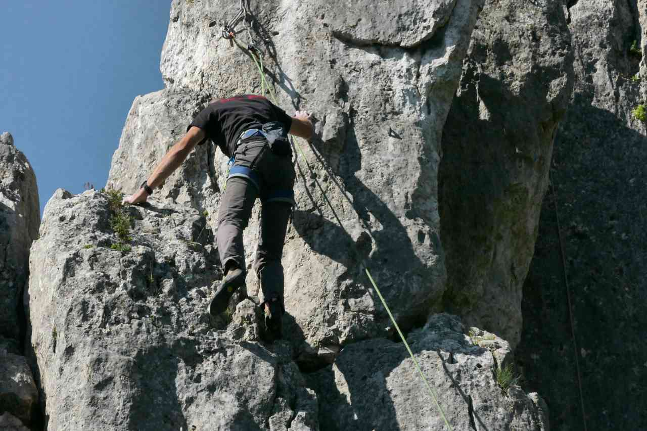 A man in harness climbing up the side of a rock formation
