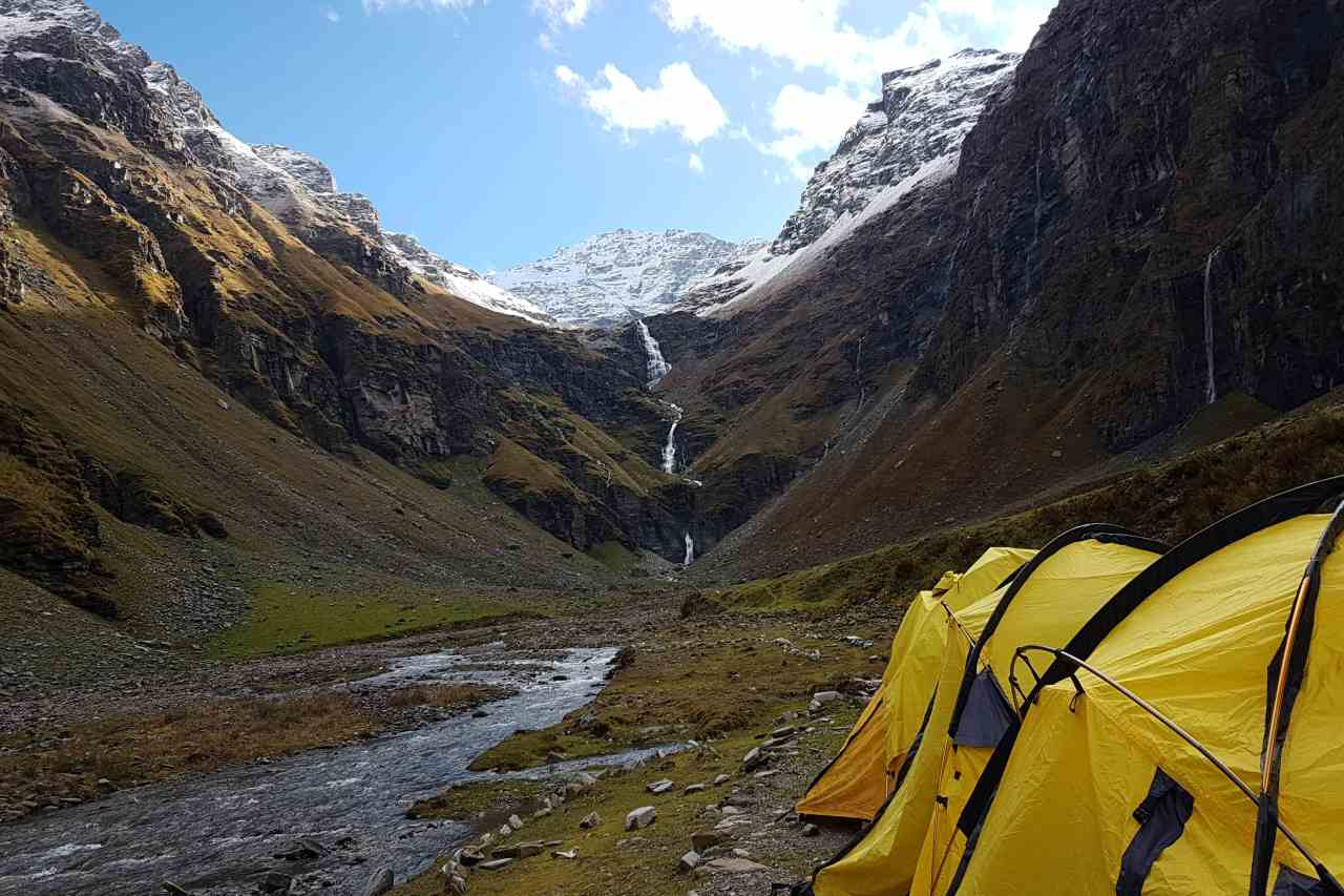 A row of yellow tents pitched on the bank of a river, fed by a waterfall