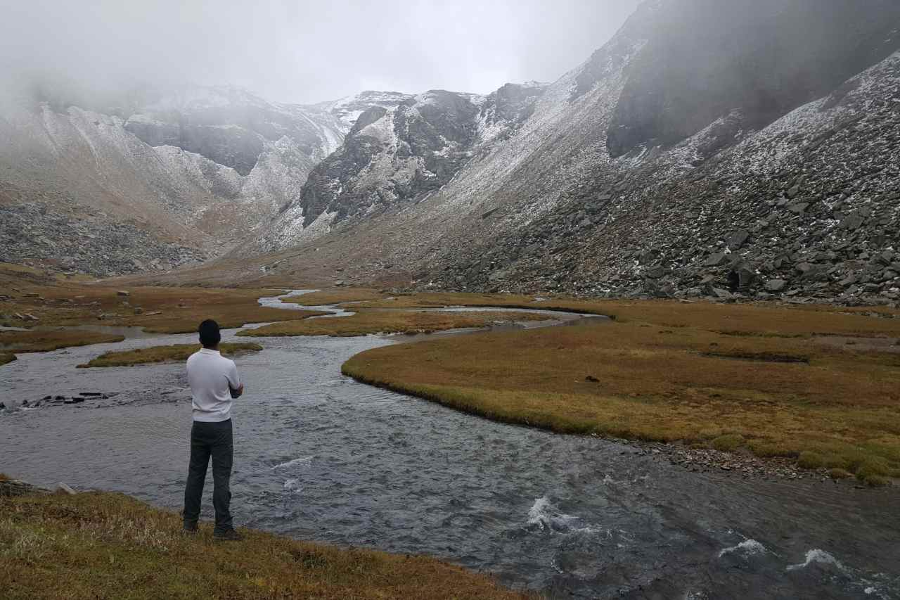A person standing on the fringe of a snaking river, surrounded by mountains