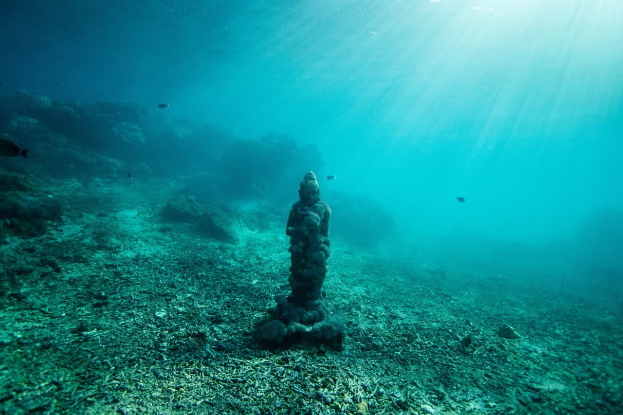 Rays of light fall on underwater statue