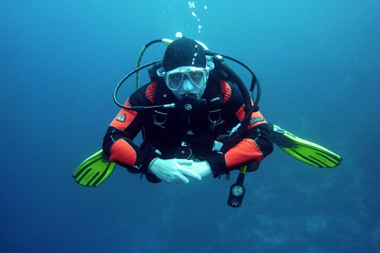 A scuba diver looks directly at the camera