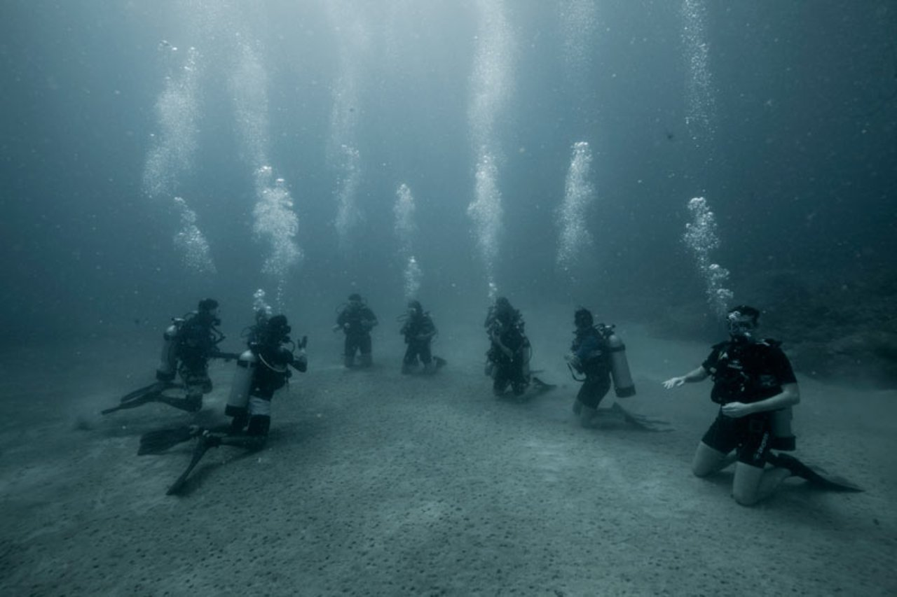 A group of scuba divers kneeling on the sea bed
