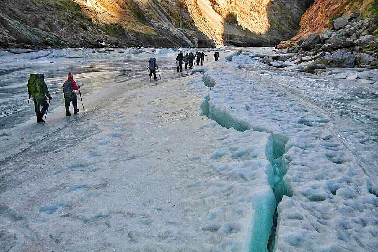 A couple of trekkers with trekking poles walking on a river of ice.